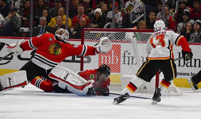 Calgary Flames left wing Johnny Gaudreau (13) scores a goal past Chicago Blackhawks goaltender Collin Delia, left, and center Dylan Strome (17) during the first period of an NHL hockey game on Monday Jan. 7, 2019, in Chicago. (AP Photo/Matt Marton)
