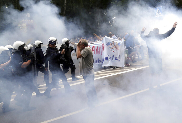 Police use tear gas at a group of young men who were trying to block the first LGBT pride parade in the eastern Polish city of Bialystok, Poland, on Saturday, July 20, 2019. (AP Photo)