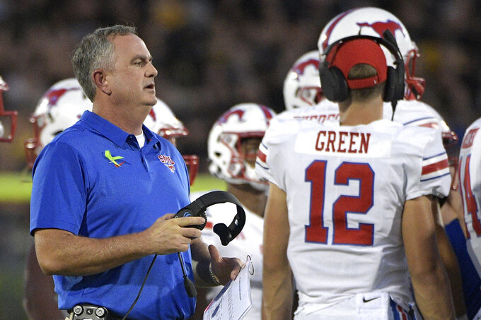SMU head coach Sonny Dykes, left, talks to his players during a timeout in the first half of an NCAA college football game against Central Florida Saturday, Oct. 6, 2018, in Orlando, Fla. (AP Photo/Phelan M. Ebenhack)