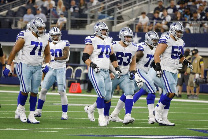 Dallas Cowboys' La'el Collins (71), Tony Pollard (20), Zack Martin (70), Tyler Biadasz (63), Tyron Smith (77) and Connor Williams (52) step up to the line of scrimmage in the first half of a preseason NFL football game against the Houston Texans in Arlington, Texas, Saturday, Aug. 21, 2021. (AP Photo/Michael Ainsworth)