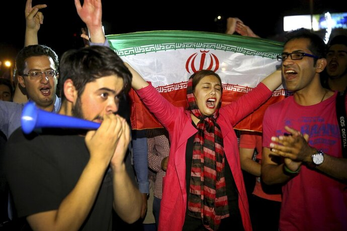 "FILE - In this July 14, 2015 file photo, an Iranian woman holds up a national flag as people celebrate a landmark nuclear deal, in Tehran, Iran. The race for the White House could mean another four years of President Donald Trump's ""maximum pressure"" campaign of crippling sanctions. Or it could bring Joe Biden, who has raised the possibility of the U.S. returning to Iran's 2015 nuclear deal with world powers. (AP Photo/Ebrahim Noroozi, File)"
