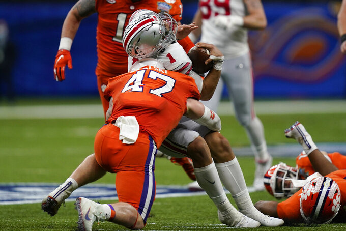 Ohio State quarterback Justin Fields gets hit by Clemson linebacker James Skalski during the first half of the Sugar Bowl NCAA college football game Friday, Jan. 1, 2021, in New Orleans. Skalski was ejected from the game for targeting. (AP Photo/Gerald Herbert)