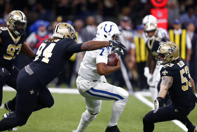 Indianapolis Colts quarterback Jacoby Brissett (7) carries between New Orleans Saints defensive end Cameron Jordan (94) and outside linebacker A.J. Klein (53) in the first half of an NFL football game in New Orleans, Monday, Dec. 16, 2019. (AP Photo/Butch Dill)