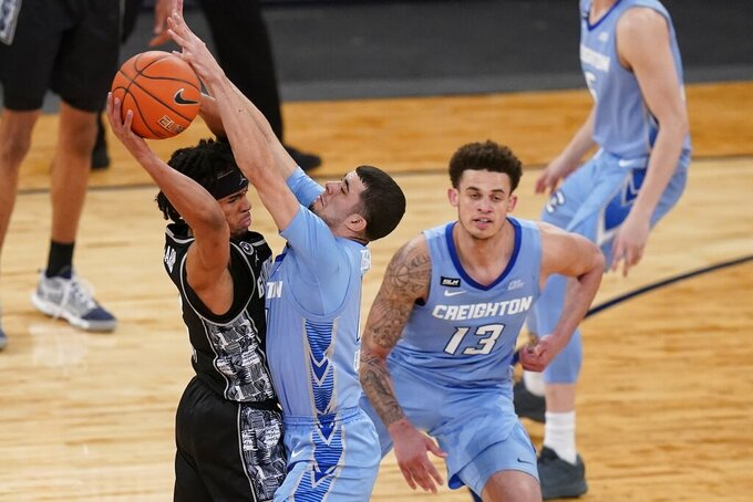 Georgetown's Dante Harris, left, passes away from Creighton's Marcus Zegarowski, center, and Christian Bishop, right, during the second half of an NCAA college basketball game in the championship of the Big East Conference tournament Saturday, March 13, 2021, in New York. (AP Photo/Frank Franklin II)