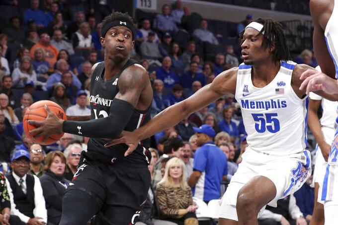 Memphis' forward Precious Achiuwa (55) defends Cincinnati's forward Tre Scott (13) in the first half of an NCAA college basketball game Thursday, Jan. 16, 2020, in Memphis, Tenn. (AP Photo/Karen Pulfer Focht)