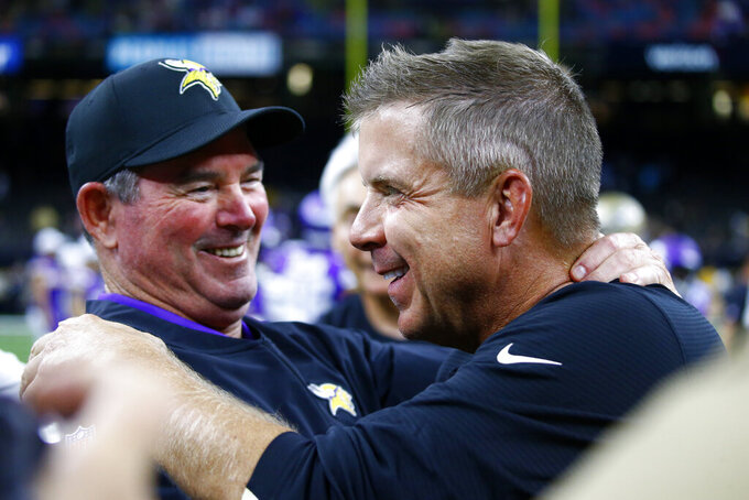Minnesota Vikings head coach Mike Zimmer, left, hugs New Orleans Saints head coach Sean Payton after an NFL preseason football game in New Orleans, Friday, Aug. 9, 2019. The Vikings won 34-25. (AP Photo/Butch Dill)