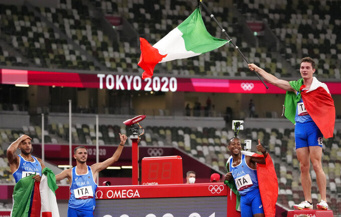 From right: Filippo Tortu, Eseosa Desalu, Lorenzo Patta and Lamont Jacobs, of Italy celebrate after taking the gold medal in the final of the men's 4 x 100-meter relay at the 2020 Summer Olympics, Friday, Aug. 6, 2021, in Tokyo, Japan. (AP Photo/Charlie Riedel)