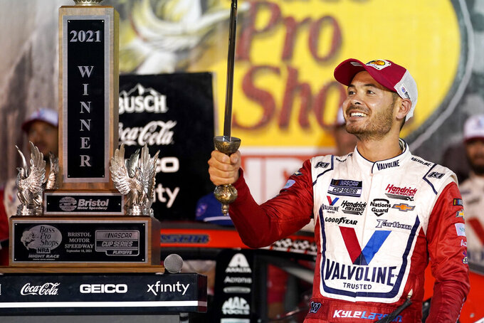 Kyle Larson accepts the sword and trophy presented to him after winning a NASCAR Cup Series auto race at Bristol Motor Speedway Saturday, Sept. 18, 2021, in Bristol, Tenn. (AP Photo/Mark Humphrey)