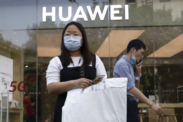 Residents wearing masks to curb the spread of the coronavirus past by a Huawei shop in Beijing on Friday, June 5, 2020. China on Wednesday demanded Washington stop