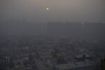 FILE - In this Jan. 2, 2021, file photo, the morning sun is seen through a blanket of smog on the outskirts of New Delhi, India. India has ambitions to expand use of electric vehicles to wean itself from polluting fossil fuels, but EVs are still a rarity on its congested highways. A lack of charging stations and poor quality batteries are discouraging drivers from switching over. (AP Photo/Altaf Qadri, File)