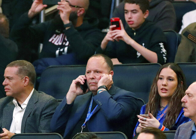 Former player agent and new New York Knicks president Leon Rose, center, takes a phone call during the first quarter of an NBA basketball game against the Houston Rockets in New York, Monday, March 2, 2020. (AP Photo/Kathy Willens)