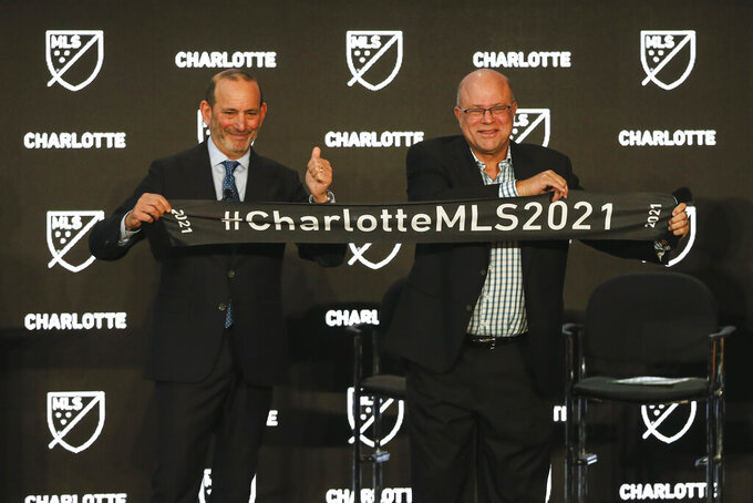 Major League Soccer Commissioner Don Garber, left, and Charlotte MLS team owner David Tepper announce that Major League Soccer will be coming to Charlotte in 2021 at an event in Charlotte, N.C., Tuesday, Dec. 17, 2019. (AP Photo/Nell Redmond