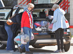 Erie Benedictine Sister Pat Lupo, left, with other volunteers, carries packages of basic care items for the first group of migrant children, about 146 girls, at the Pennsylvania International Academy dorms, Tuesday, April 13, 2021, in Summit Township, Pa. Most of the items appeared to be clothing for the children, ages 7-12, arriving from the U.S-Mexico border. (Greg Wohlford/Erie Times-News via AP)