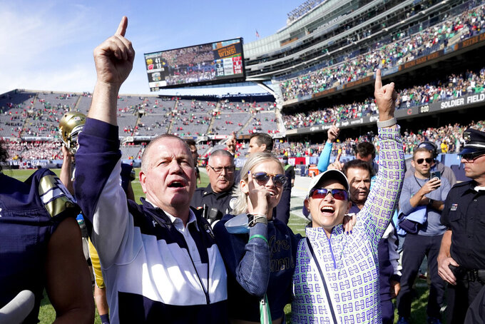 Notre Dame head coach Brian Kelly, left, daughter Grace, center, and wife Paqui, celebrate Notre Dame's 41-13 win over Wisconsin after an NCAA college football game Saturday, Sept. 25, 2021, in Chicago. (AP Photo/Charles Rex Arbogast)