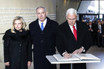 United States Vice President Mike Pence writes in the guest book beside Israeli Prime Minister Benjamin Netanyahu and his wife Sara, at the Monument to the Ghetto Heroes after a wreath laying ceremony in Warsaw, Poland, Thursday, Feb. 14, 2019. The Polish capital is host for a two-day international conference on the Middle East, co-organized by Poland and the United States. (AP Photo/Michael Sohn)