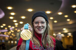 FILE - In this Feb. 26, 2018, file photo, freestyle skier Cassie Sharpe, of Canada, holds her 2018 Olympic gold medal after arriving from South Korea at Vancouver International Airport in Richmond, B.C. Sharpe was name-dropped in a tweet by movie star Ryan Reynolds, saw a little girl dressed up as her for Halloween and even got her face on a pair of socks owned by the prime minister. These things can happen when you win Olympic gold. (Darryl Dyck/The Canadian Press via AP, File)