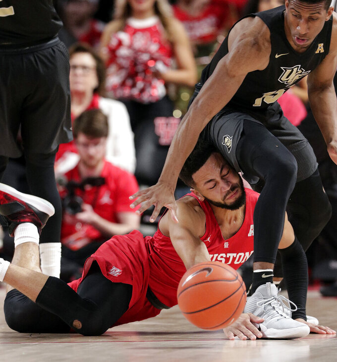Houston guard Galen Robinson Jr., left, collides with Central Florida guard Aubrey Dawkins (15) as he loses his footing during the first half of an NCAA college basketball game Saturday, March 2, 2019, in Houston. (AP Photo/Michael Wyke)