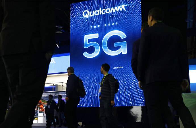 "FILE- In this Jan. 9, 2019, file photo a sign advertises 5G at the Qualcomm booth at CES International in Las Vegas. 5G is a new technical standard for wireless networks that promises faster speeds; less lag, or ""latency,"" when connecting to the network; and the ability to connect many devices to the internet without bogging it down. (AP Photo/John Locher, File)"