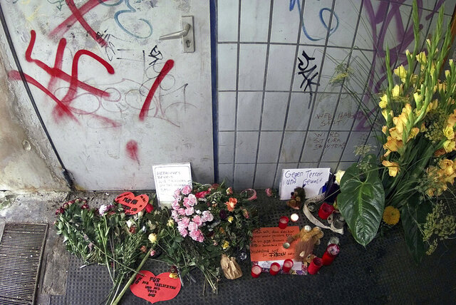 FILE - In this file photo dated Thursday, Aug. 3, 2000, flowers and candle tributes at a memorial beside the scene of an explosion that took place last Thursday, in Duesseldorf, Germany.  A bomb explosion at a commuter train station on Thursday July 27 injured many, two of them seriously and unborn child died. In a deadly shooting late Wednesday Feb. 19, 2020, German authorities suspect that the gunman who killed several people with migrant backgrounds in the Frankfurt suburb of Hanau was motivated by racism, the latest in a long line of far-right attacks in Germany, a country still grappling with its Nazi past. (AP Photo/Edgar R.Schoepal, FILE)
