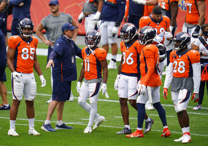 Denver Broncos quarterbacks coach Mike Shula, second from left, directs, from left to right, tight end Albert Okwuegbunam, wide receivers Diontae Spencer, Tyrie Cleveland and DaeSean Hamilton and running back Royce Freeman in a drill during an NFL football practice in empty Empower Field at Mile High, Saturday, Aug. 29, 2020, in Denver. (AP Photo/David Zalubowski)