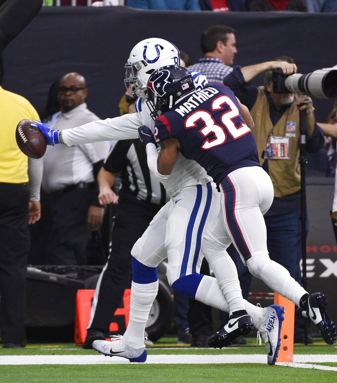Indianapolis Colts tight end Eric Ebron, left, is hit by Houston Texans free safety Tyrann Mathieu (32) as he score a touchdown during the first half of an NFL wild card playoff football game, Saturday, Jan. 5, 2019, in Houston. (AP Photo/Eric Christian Smith)