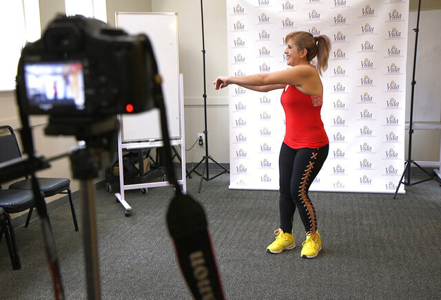 In this Tuesday, March 17, 2020 photo, dance instructor Lola Jaramillo records a Zumba and exercise lesson in Washington, that will be uploaded in the social media accounts of Vida Senior Center, a nonprofit that serves Washington's older Hispanic community. (AP Photo/Federica Narancio)