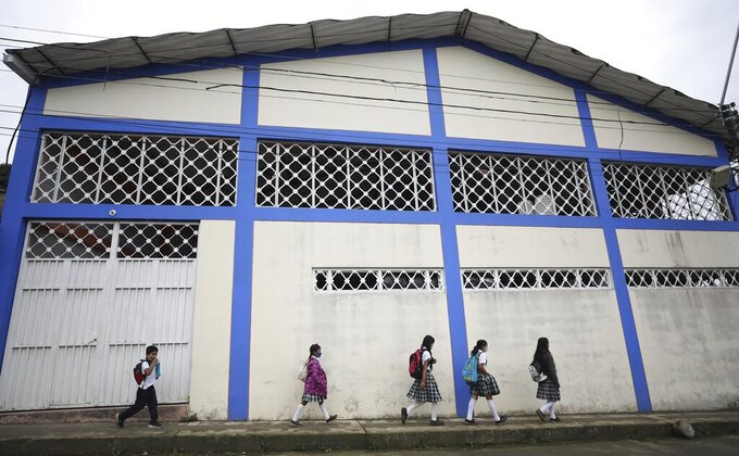 Wearing masks to curb the spread of the new coronavirus, students walk to the only open school in Campohermoso, Colombia, Thursday, March 18, 2021. Campohermoso is one of two municipalities in Colombia that has not had a single case of COVID-19 since the pandemic started one year ago, with the student body at the school rotating half the students into their classrooms while the other attends via the internet. (AP Photo/Fernando Vergara)