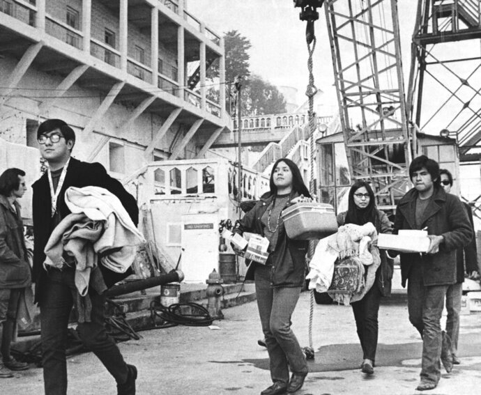 FILE - In this Dec. 2, 1969, file photo, a new group of arrivals walks across the docking area with handfuls of possessions during the Native American occupation of Alcatraz Island in San Francisco. The week of Nov. 18, 2019, marks 50 years since the beginning of a months-long Native American occupation at Alcatraz Island in the San Francisco Bay. The demonstration by dozens of tribal members had lasting effects for tribes, raising awareness of life on and off reservations, galvanizing activists and spurring a shift in federal policy toward self-determination. (AP Photo/RWK, File)
