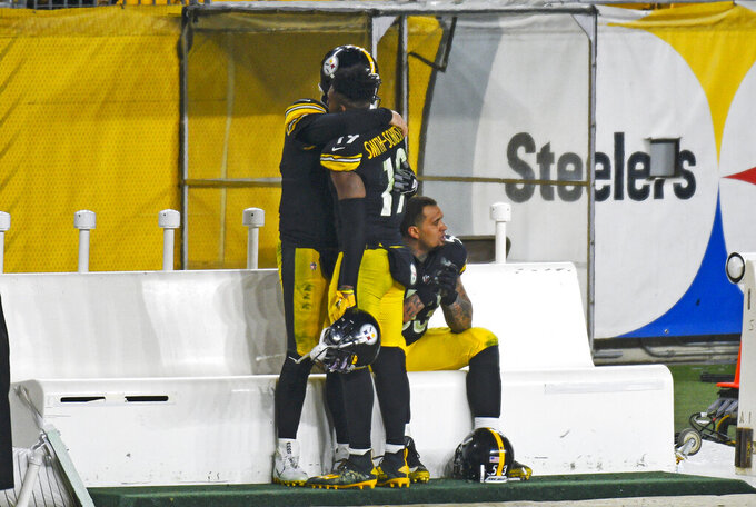 Pittsburgh Steelers quarterback Ben Roethlisberger, rear left, hugs wide receiver JuJu Smith-Schuster (19) after a 48-37 loss to the Cleveland Browns in an NFL wild-card playoff football game in Pittsburgh, Sunday, Jan. 10, 2021. (AP Photo/Don Wright)
