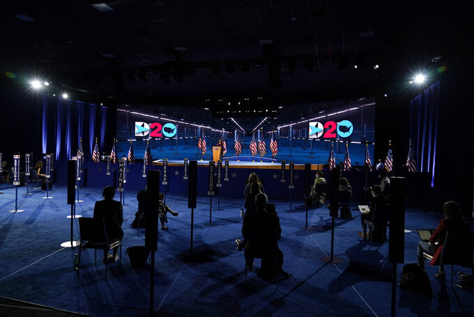 Reporters sit and listen as Democratic vice presidential candidate Sen. Kamala Harris, D-Calif., speaks during the third day of the Democratic National Convention, Wednesday, Aug. 19, 2020, at the Chase Center in Wilmington, Del. (AP Photo/Carolyn Kaster)