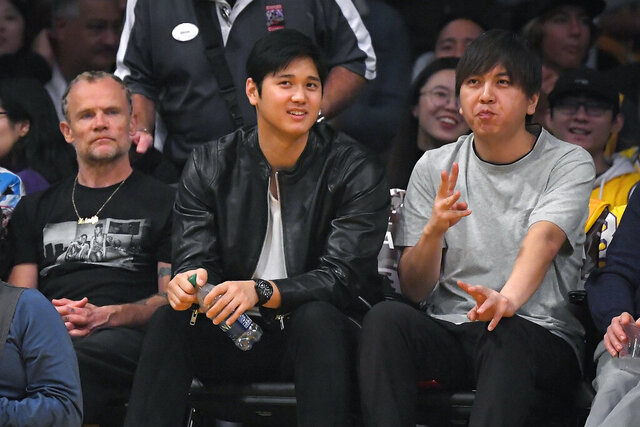 Los Angeles Angels pitcher Shohei Ohtani, center, watches along with Flea, left, of the Red Hot Chili Peppers, and Ohtani's interpreter Ippei Mizuhara during the second half of an NBA basketball game between the Los Angeles Lakers and the Washington Wizards, Friday, Nov. 29, 2019, in Los Angeles. The Lakers won 125-103. (AP Photo/Mark J. Terrill)