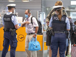 Federal police officers check passengers arriving aboard a flight from Portugal, at Frankfurt airport, Germany, Tuesday June 29, 2021. As of Tuesday, Portugal is being considered a virus variant area, and people arriving in Germany must go into quarantine. (Boris Roessler/dpa via AP)