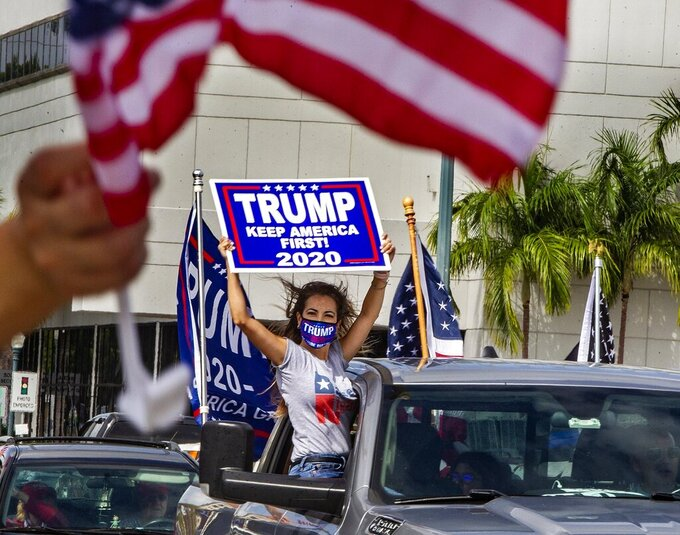 In this Oct. 10, 2020, a caravan in favor of President Trump drives down the Little Havana neighborhood of Miami. Florida's Cuban American voters remain a bright spot in Trump's effort to retain his winning coalition from 2016. Polls show his strong support from these key voters may even be growing to include the younger Cuban Americans that Democrats once considered their best hope of breaking the GOP's hold.  (Pedro Portal/Miami Herald via AP)