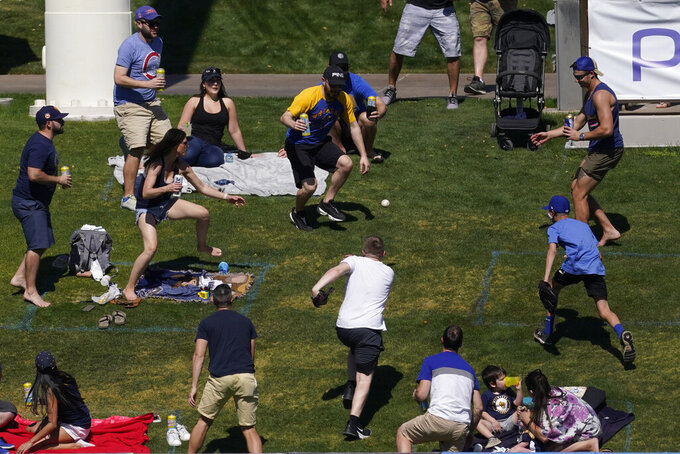 Fans run to retrieve a home run ball hit by Chicago Cubs' Joc Pederson during the third inning of a spring training baseball game against the Milwaukee Brewers Saturday, March 6, 2021, in Phoenix. (AP Photo/Ashley Landis)