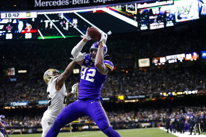 Minnesota Vikings tight end Kyle Rudolph (82) pulls in the game winning touchdown pass over New Orleans Saints cornerback P.J. Williams (26) during overtime of an NFL wild-card playoff football game, Sunday, Jan. 5, 2020, in New Orleans. The Vikings won 26-20. (AP Photo/Brett Duke)