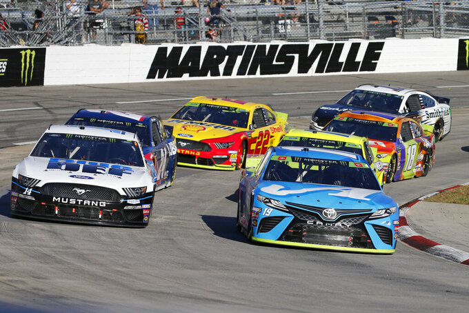 FILE - In this Oct. 27, 2019, file photo, Martin Truex Jr. (19) and Clint Bowyer (14) lead the field in turn four during a restart of the NASCAR Cup Series race at Martinsville Speedway in Martinsville, Va. NASCAR will race at Martinsville Speedway on Wednesday, June 10, 2020. (AP Photo/Steve Helber)