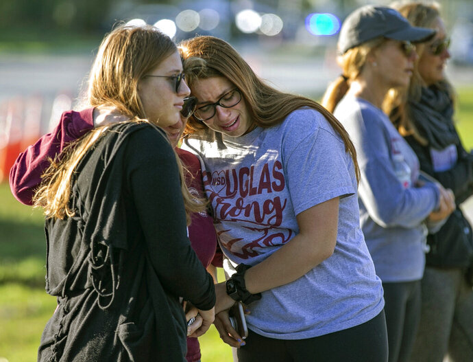 Emma Rothenberg, from left to right, with her mother Cheryl Rothenberg and sister, Marjory Stoneman Douglas High School student Sophia Rothenberg, embrace at a memorial marking the one-year anniversary of a mass shooting at the school in Parkland, Fla., on Thursday, Feb. 14, 2019. (Al Diaz/Miami Herald via AP)
