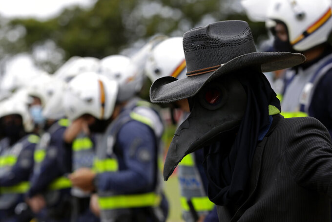 A demonstrator dressed in a bird mask, representing the black plague, stands near police guarding a city government office where demonstrators protest a two-week-long lockdown to curb the spread of COVID-19 in Brasilia, Brazil, Monday, March 1, 2021. It's the second lockdown in Brasilia since the start of the pandemic one year ago. (AP Photo/Eraldo Peres)