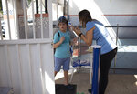 A teacher checks the temperature of Bernardo Santo as he arrives at the Pereira Agustinho daycare, nursery school and pre-school, after it reopened amid the new coronavirus pandemic in Duque de Caxias, Monday, July 6, 2020. The city of Manaus in the Amazon rainforest and Duque de Caxias in Rio de Janeiro's metropolitan region, became on Monday the first Brazilian cities to resume in-person classes at private schools since the onset of the COVID-19 pandemic, according to the nation's private school federation. (AP Photo/Silvia Izquierdo)