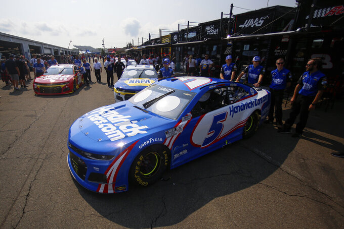 Cars, including Kyle Larson's (5), Chase Elliott's (9) and Daniel Suarez's, left, wait in line for an inspection before a NASCAR Cup Series auto race in Watkins Glen, N.Y., on Sunday, Aug. 8, 2021. (AP Photo/Joshua Bessex)