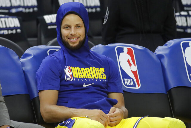 FILE - In this Thursday, Feb. 27, 2020 file photo, Golden State Warriors guard Stephen Curry smiles on the bench as players warm up before an NBA basketball game between the Warriors and the Los Angeles Lakers in San Francisco. Stephen Curry had hoped to play for the Warriors on Sunday, March 1, 2020 at home against the Washington Wizards, but he won't return quite yet from a broken left hand. The two-time NBA MVP has been sidelined the past four months. (AP Photo/Jeff Chiu, File)