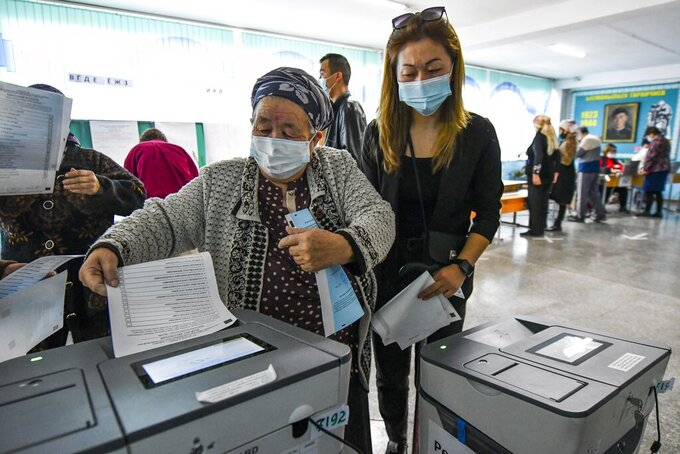 A woman casts her ballot at a polling station during the referendum in Bishkek, Kyrgyzstan, Sunday, April 11, 2021. Voters in Kyrgyzstan cast ballots Sunday on whether to approve a new constitution that would substantially increase the president's powers. The Sunday referendum comes three months after Sadyr Zhaparov was elected president, following the ouster of the previous president amid protests, the third time in 15 years that a leader of the Central Asian country had been driven from office in a popular uprising. (AP Photo/Vladimir Voronin)