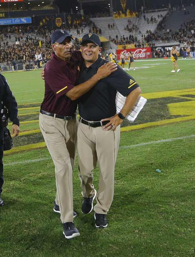 Arizona State head coach Herm Edwards, left, celebrates a win against Michigan State with defensive coordinator Danny Gonzales, right, after an NCAA college football game Saturday, Sept. 8, 2018, in Tempe, Ariz. Arizona State defeated Michigan State 16-13. (AP Photo/Ross D. Franklin)