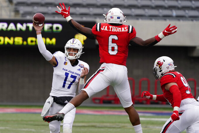 San Jose State quarterback Nick Starkel (17) throws around Ball State linebacker Jaylin Thomas (6) during the second half of the Arizona Bowl NCAA college football game Thursday, Dec. 31, 2020, in Tucson, Ariz. Ball State won 34-13. (AP Photo/Rick Scuteri)