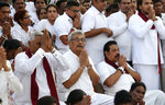 In this Aug 15, 2019, photo, former Sri Lankan Defense Secretary and opposition's presidential candidate Nandasena Gotabaya Rajapaksa, center, along with his brothers Chamal, left, and Mahinda, right, prays at a Buddhist temple during his election campaign in Anuradhapura, Sri Lanka. Gotabaya is a feared former defense official accused of human rights abuses and crushing critics, but to many Sri Lankans, he is the leader most needed after last April's Easter bomb attacks that killed more than 250 people. (AP Photo/Sajeewa Chinthaka)