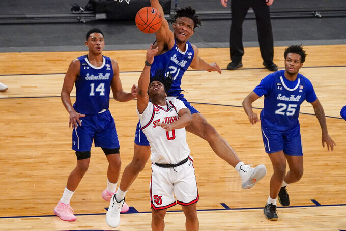 St. John's guard Posh Alexander (0) goes to the basket against Seton Hall center Ike Obiagu (21) during the second half of an NCAA college basketball game in the quarterfinals of the Big East conference tournament, Thursday, March 11, 2021, in New York. (AP Photo/Mary Altaffer)