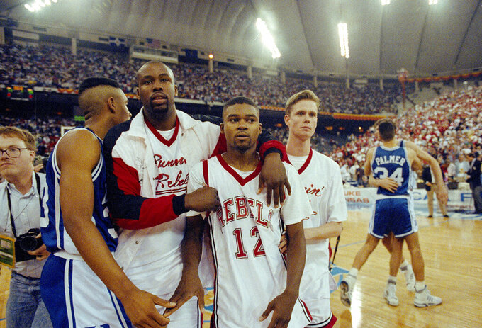FILE - In this March 30, 1991, file photo, UNLV's Anderson Hunt (12) and unidentified teammates leave the floor after losing to Duke in an NCAA national semifinal game in Indianapolis. UNLV came down court with one final chance at keeping its dreams alive, but Anderson Hunt's 3-pointer with 2 seconds to play bounced off the rim. (AP Photo/Al Behrman, File)