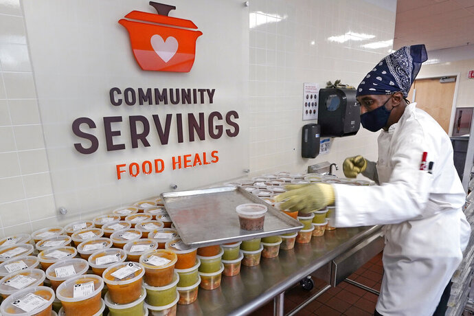 Chef Jermaine Wall stacks containers of soups at Community Servings, which prepares and delivers scratch-made, medically tailored meals to individuals & families living with critical & chronic illnesses, Tuesday, Jan. 12, 2021, in the Jamaica Plain neighborhood of Boston. Food is a growing focus for insurers as they look to improve the health of the people they cover and cut costs. Insurers first started covering Community Servings meals about five years ago, and CEO David Waters says they now cover close to 40%. (AP Photo/Charles Krupa)