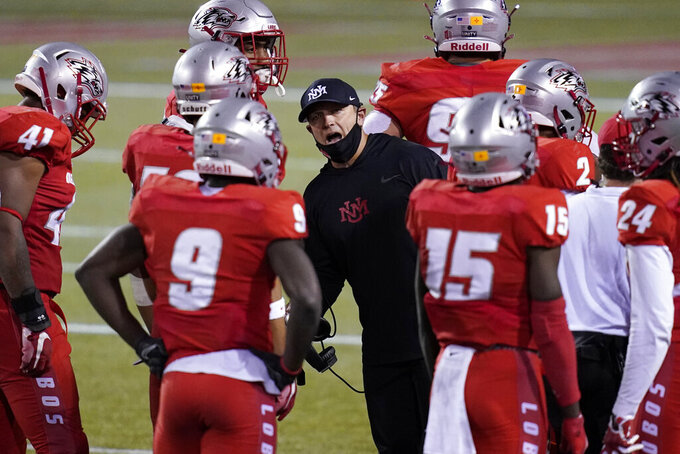FILE - In this Saturday, Nov. 14, 2020, file photo, New Mexico head coach Danny Gonzales speaks with players during the second half of an NCAA college football game against Nevada, in Las Vegas. Coronavirus restrictions in New Mexico make it impossible for the schools there to play their seasons. New Mexico's football team was the first to temporarily relocate, moving to the Las Vegas area to practice and play. (AP Photo/John Locher, File)