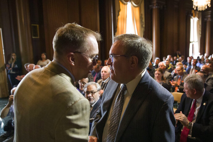 Acting White House Chief of Staff Mick Mulvaney, left, shakes hands with EPA administrator Andrew Wheeler after Wheeler signed the Affordable Clean Energy Rule at the Environmental Protection Agency, Wednesday, June 19, 2019, in Washington. Wheeler signed a repeal of one of the Obama era's two biggest climate change initiatives, the Clean Power Plan, and adopting an alternative plan that would loosen regulations on the plants. (AP Photo/Alex Brandon)
